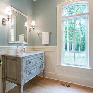 На фото: туалет среднего размера в классическом стиле с фасадами островного типа, искусственно-состаренными фасадами, синими стенами, светлым паркетным полом, врезной раковиной и мраморной столешницей
