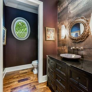 На фото: туалеты среднего размера с фасадами островного типа, коричневыми фасадами, раздельным унитазом, коричневой плиткой, керамогранитной плиткой, коричневыми стенами, паркетным полом среднего тона, настольной раковиной, столешницей из искусственного кварца, коричневым полом и черной столешницей