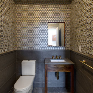 Inspiration for a small contemporary cloakroom in New York with a two-piece toilet, grey tiles, multi-coloured walls, slate flooring, solid surface worktops and a submerged sink.