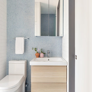Nordische Gästetoilette mit flächenbündigen Schrankfronten, hellen Holzschränken, Toilette mit Aufsatzspülkasten, blauen Fliesen, Mosaikfliesen, blauer Wandfarbe, Mosaik-Bodenfliesen und blauem Boden in New York