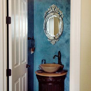 Diseño de aseo bohemio, de tamaño medio, con armarios tipo mueble, puertas de armario de madera en tonos medios, paredes azules, lavabo sobreencimera, sanitario de una pieza, suelo de madera en tonos medios y encimera de travertino