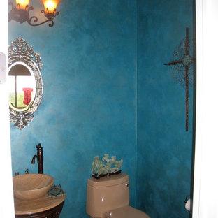 Eklektisk inredning av ett mellanstort toalett, med möbel-liknande, skåp i mörkt trä, blå väggar, ett fristående handfat, en toalettstol med hel cisternkåpa, mellanmörkt trägolv och bänkskiva i travertin