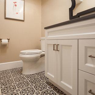 На фото: туалет среднего размера в стиле фьюжн с фасадами в стиле шейкер, белыми фасадами, раздельным унитазом, бежевыми стенами, полом из керамогранита, врезной раковиной, столешницей из искусственного кварца, зеленым полом и черной столешницей с