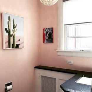 Пример оригинального дизайна: маленький туалет в стиле фьюжн с фасадами с декоративным кантом, белыми фасадами, раздельным унитазом, розовыми стенами, полом из бамбука, врезной раковиной, столешницей из искусственного кварца и серым полом