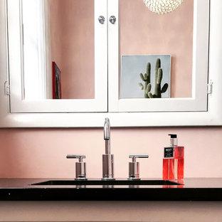 Réalisation d'un petit WC et toilettes bohème avec un placard à porte affleurante, des portes de placard blanches, un WC séparé, un mur rose, un sol en bambou, un lavabo encastré, un plan de toilette en quartz modifié et un sol gris.