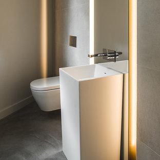 Exemple d'un WC et toilettes tendance de taille moyenne avec une vasque, un WC suspendu, un carrelage gris, des carreaux de porcelaine, un mur gris et béton au sol.
