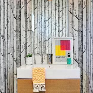 Ejemplo de aseo retro con armarios con paneles lisos, puertas de armario de madera clara y lavabo integrado