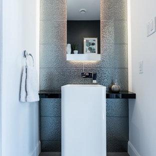 На фото: туалет среднего размера в современном стиле с плоскими фасадами, белыми фасадами, керамической плиткой, белыми стенами, полом из керамической плитки, столешницей из ламината, серым полом, серой плиткой и раковиной с пьедесталом
