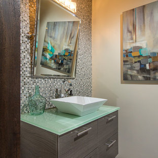 Example of a trendy multicolored tile and mosaic tile medium tone wood floor powder room design in San Diego with a vessel sink, flat-panel cabinets, gray cabinets, glass countertops, beige walls and green countertops