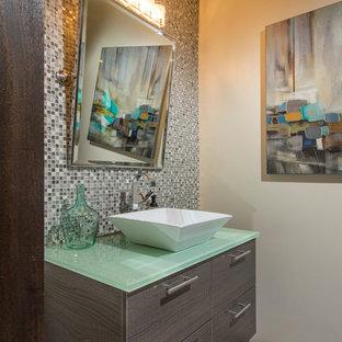 Стильный дизайн: туалет в современном стиле с настольной раковиной, плоскими фасадами, серыми фасадами, стеклянной столешницей, разноцветной плиткой, плиткой мозаикой, бежевыми стенами, паркетным полом среднего тона и зеленой столешницей - последний тренд
