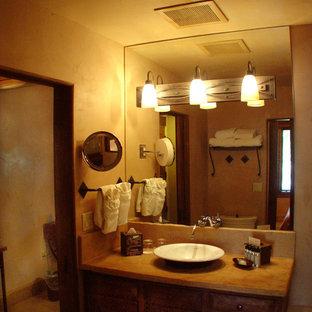 Immagine di un bagno di servizio stile americano di medie dimensioni con ante con bugna sagomata, ante in legno bruno, WC a due pezzi, pareti beige, pavimento in terracotta, lavabo a bacinella, top in cemento e pavimento rosso