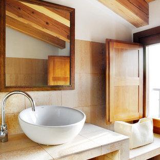 Ejemplo de aseo rústico, pequeño, con baldosas y/o azulejos beige, baldosas y/o azulejos de cerámica, paredes blancas, lavabo sobreencimera y encimera de azulejos