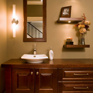 Large transitional travertine floor powder room photo in Calgary with raised-panel cabinets, dark wood cabinets, beige walls, a vessel sink and wood countertops