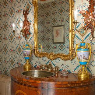 Пример оригинального дизайна: огромный туалет в викторианском стиле с фасадами островного типа, темными деревянными фасадами, бежевой плиткой, керамогранитной плиткой, разноцветными стенами, темным паркетным полом, накладной раковиной, столешницей из дерева и раздельным унитазом