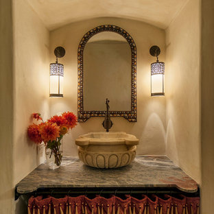 Example of a tuscan powder room design in Santa Barbara with beige walls, marble countertops and a vessel sink