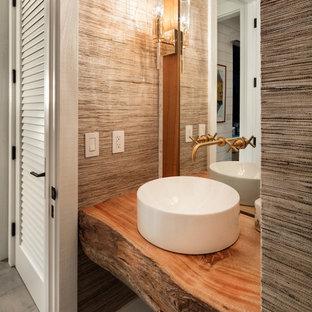 Exemple d'un petit WC et toilettes bord de mer avec un placard sans porte, des portes de placard en bois clair, un WC à poser, un carrelage blanc, carrelage en mosaïque, un mur blanc, un sol en carrelage de céramique, une vasque, un plan de toilette en bois, un sol gris et un plan de toilette marron.