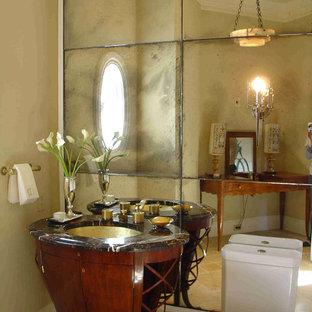 Imagen de aseo retro, pequeño, con lavabo bajoencimera, armarios tipo mueble, puertas de armario de madera oscura, encimera de ónix, sanitario de una pieza, baldosas y/o azulejos beige, paredes beige, suelo de piedra caliza y baldosas y/o azulejos con efecto espejo