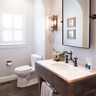 Свежая идея для дизайна: туалет в стиле кантри с фасадами островного типа, темными деревянными фасадами, раздельным унитазом, серыми стенами, темным паркетным полом, врезной раковиной, коричневым полом и белой столешницей - отличное фото интерьера