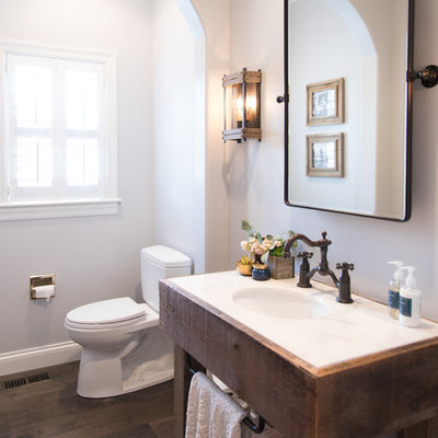 Inspiration for a country dark wood floor and brown floor powder room remodel in St Louis with furniture-like cabinets, dark wood cabinets, a two-piece toilet, gray walls, an undermount sink and white countertops