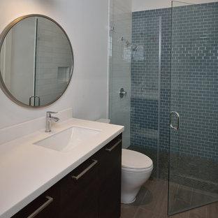 Inspiration pour un WC et toilettes de taille moyenne avec un placard à porte plane, des portes de placard marrons, un WC à poser, un carrelage bleu, des carreaux de céramique, un mur blanc, un sol en carrelage de porcelaine, un lavabo encastré, un plan de toilette en acier inoxydable et un sol marron.