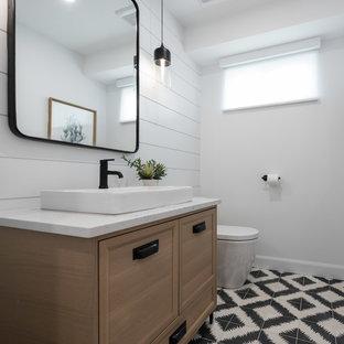 На фото: туалет в стиле кантри с фасадами островного типа, светлыми деревянными фасадами, белыми стенами, полом из цементной плитки, настольной раковиной, столешницей из кварцита и черным полом с