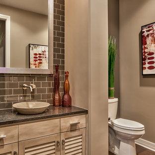 オマハの中くらいのトランジショナルスタイルのおしゃれなトイレ・洗面所 (ルーバー扉のキャビネット、淡色木目調キャビネット、分離型トイレ、茶色い壁、無垢フローリング、ベッセル式洗面器、茶色いタイル、サブウェイタイル、御影石の洗面台、茶色い床) の写真