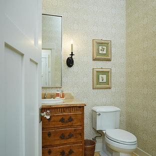 На фото: большой туалет в классическом стиле с темными деревянными фасадами, разноцветными стенами, полом из керамической плитки, накладной раковиной, фасадами островного типа, унитазом-моноблоком и желтым полом с