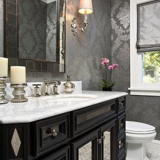Diseño de aseo clásico con lavabo bajoencimera, armarios con paneles empotrados, puertas de armario negras y encimeras blancas