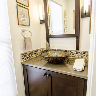 Photo of a small traditional cloakroom in DC Metro with a vessel sink, shaker cabinets, dark wood cabinets, engineered stone worktops, a two-piece toilet, multi-coloured tiles, pebble tiles, porcelain flooring, white walls and white floors.