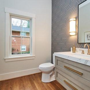 ワシントンD.C.の中くらいのトランジショナルスタイルのおしゃれなトイレ・洗面所 (シェーカースタイル扉のキャビネット、白いキャビネット、分離型トイレ、マルチカラーの壁、無垢フローリング、アンダーカウンター洗面器、クオーツストーンの洗面台、茶色い床、白い洗面カウンター、フローティング洗面台、壁紙) の写真