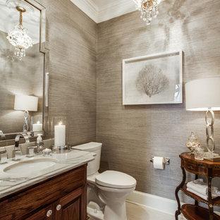 Cette image montre un WC et toilettes traditionnel de taille moyenne avec un placard avec porte à panneau surélevé, des portes de placard en bois sombre, un WC à poser, un mur gris et un lavabo encastré.