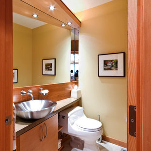 Small contemporary cloakroom in Portland with flat-panel cabinets, medium wood cabinets, concrete worktops, a one-piece toilet, a vessel sink, yellow walls, limestone flooring and grey tiles.