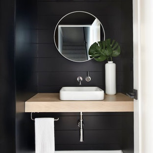 This is an example of a mid-sized transitional powder room in Denver with black walls, porcelain floors, a vessel sink, wood benchtops and multi-coloured floor.