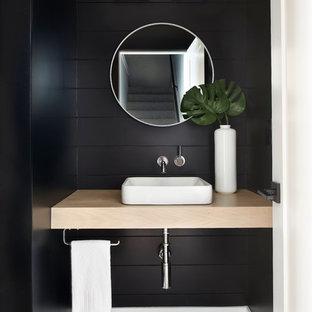 На фото: туалет среднего размера в стиле современная классика с черными стенами, полом из керамогранита, настольной раковиной, столешницей из дерева и разноцветным полом с