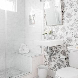 Idée de décoration pour un WC et toilettes tradition avec un carrelage blanc, un carrelage métro, un lavabo suspendu et un sol blanc.