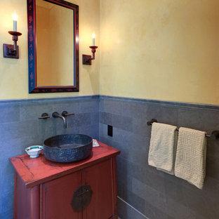 Modelo de aseo asiático con lavabo sobreencimera, baldosas y/o azulejos grises, baldosas y/o azulejos de piedra, paredes amarillas, suelo de madera clara, puertas de armario con efecto envejecido y armarios tipo mueble