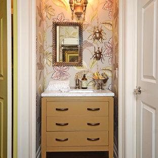 Modelo de aseo vintage, pequeño, con lavabo bajoencimera, puertas de armario beige, encimera de mármol, paredes multicolor y suelo de madera oscura
