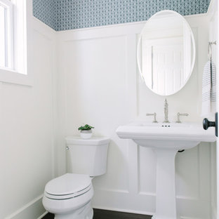 Photo of a mid-sized country powder room in Chicago with a two-piece toilet, dark hardwood floors, a pedestal sink and brown floor.