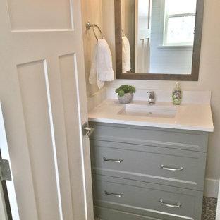 Landhaus Gästetoilette mit flächenbündigen Schrankfronten, grauen Schränken, Toilette mit Aufsatzspülkasten, weißen Fliesen, beiger Wandfarbe, Vinylboden, Unterbauwaschbecken, Quarzwerkstein-Waschtisch, buntem Boden und weißer Waschtischplatte in Vancouver