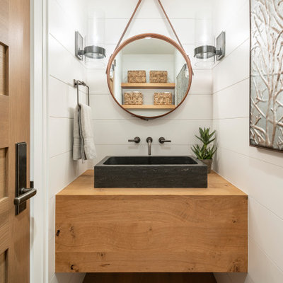 Powder room - small farmhouse medium tone wood floor and brown floor powder room idea in Salt Lake City with white walls, a vessel sink, wood countertops and brown countertops