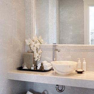 На фото: туалет в средиземноморском стиле с настольной раковиной и мраморной плиткой