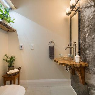トロントの中サイズのラスティックスタイルのおしゃれなトイレ・洗面所 (ベージュの壁、磁器タイルの床、ベッセル式洗面器、木製洗面台、ベージュの床、ブラウンの洗面カウンター) の写真