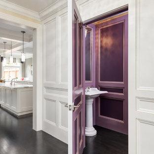 На фото: туалет в классическом стиле с раковиной с пьедесталом, фиолетовыми стенами и темным паркетным полом с