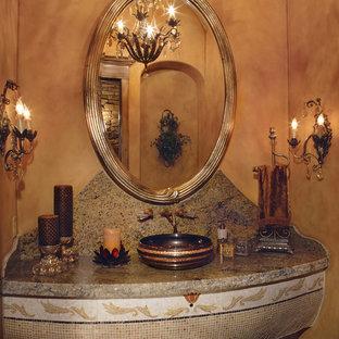 Réalisation d'un très grand WC et toilettes méditerranéen avec une vasque, un plan de toilette en granite, un WC séparé, un carrelage beige, un mur beige et un sol en travertin.