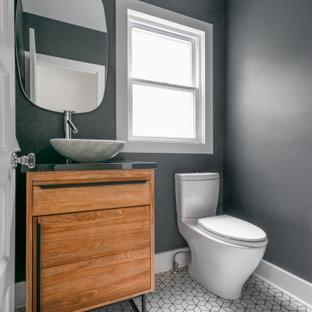 Свежая идея для дизайна: маленький туалет в стиле модернизм с фасадами островного типа, фасадами цвета дерева среднего тона, раздельным унитазом, серой плиткой, серыми стенами, полом из керамической плитки, настольной раковиной, столешницей из искусственного камня, белым полом и серой столешницей - отличное фото интерьера