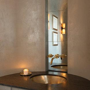 Immagine di un bagno di servizio chic di medie dimensioni con ante grigie, WC sospeso, pareti grigie, pavimento in pietra calcarea, lavabo sottopiano, top in granito, pavimento marrone e top marrone
