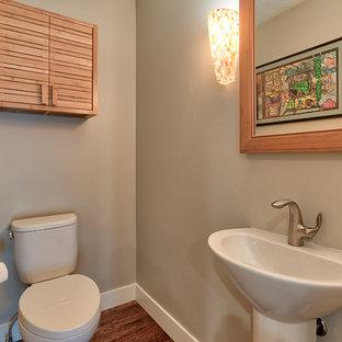 Источник вдохновения для домашнего уюта: большой туалет в стиле ретро с фасадами с филенкой типа жалюзи, светлыми деревянными фасадами, раздельным унитазом, бежевыми стенами, темным паркетным полом, раковиной с пьедесталом, столешницей из искусственного камня и коричневым полом