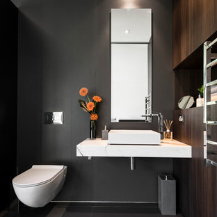 Mid-sized trendy ceramic floor powder room photo in Perth with a vessel sink, dark wood cabinets, marble countertops, a wall-mount toilet and black walls