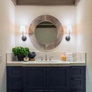 Cette image montre un petit WC et toilettes rustique avec un placard à porte shaker, des portes de placard bleues, des dalles de pierre, un mur blanc, un sol en bois foncé, un lavabo encastré et un plan de toilette en marbre.
