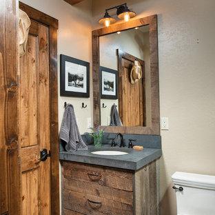 デンバーのラスティックスタイルのおしゃれなトイレ・洗面所 (フラットパネル扉のキャビネット、濃色木目調キャビネット、ベージュの壁、アンダーカウンター洗面器、グレーの床、グレーの洗面カウンター) の写真